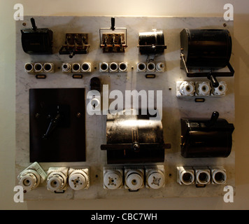An old electric fuse box switchboard with ceramic fuses - Stock Photo