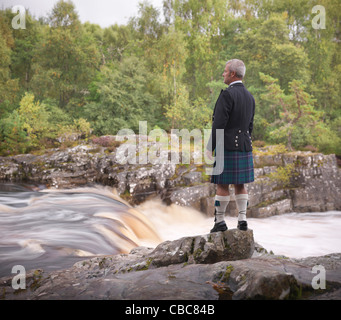 Time lapse view of man in kilt by river - Stock Photo