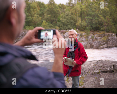 Hiker taking picture of friend by river - Stock Photo