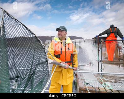 Fisherman holding net on boat - Stock Photo