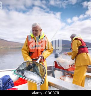 Fisherman holding salmon in net - Stock Photo