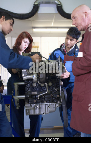 Teacher helping students with car engine - Stock Photo