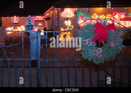 Bungalow House Lit Up At Night With Xmas Christmas Lights - Stock Photo