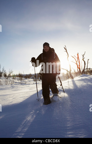 Cross-country skier walking in snow - Stock Photo