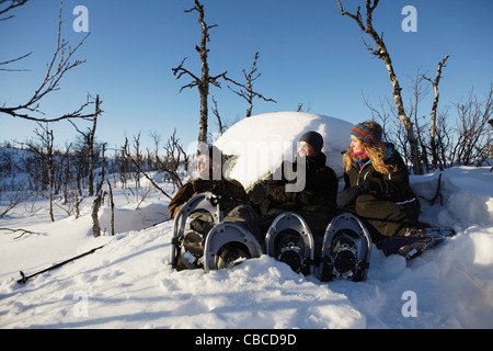 Cross-country skiers resting in snow - Stock Photo