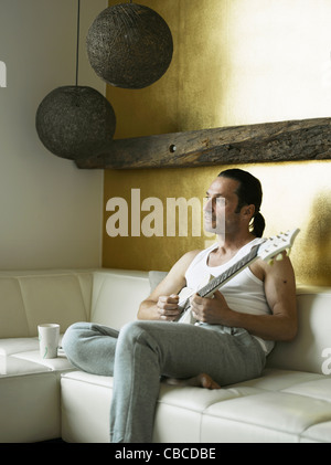 Man playing guitar on couch