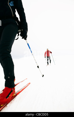 Couple cross-country skiing in snow - Stock Photo