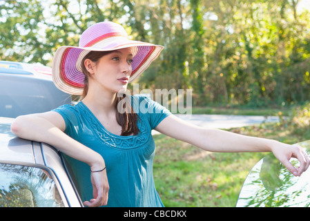 Woman standing by car on road - Stock Photo