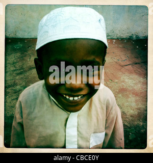 A young boy looking at camera with kofia, Lamu, Kenya - Stock Photo