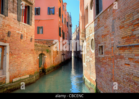 Narrow canal among old colorful houses in Venice, Italy. - Stock Photo