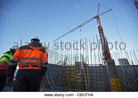 Workers talking on construction site - Stock Photo