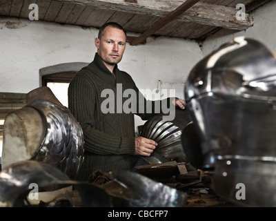 Blacksmith crafting armor in shop - Stock Photo