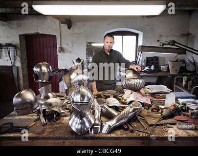 Blacksmith with armor in shop - Stock Photo