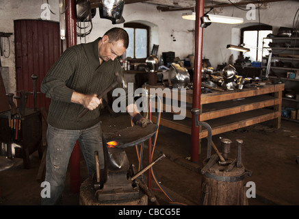 Blacksmith at work in shop - Stock Photo
