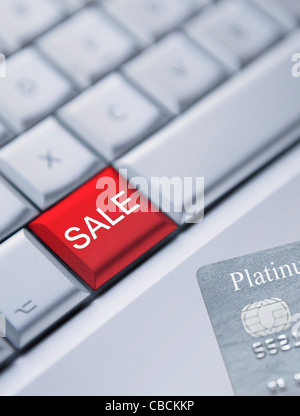 Detail of a laptop keyboard with one red key with Sale printed on it and a credit card at the bottom right corner. - Stock Photo