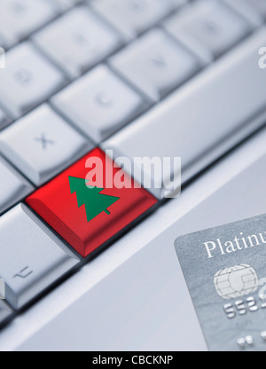 Detail of a laptop keyboard with one red key with Christmas Tree Symbol and a credit card at the bottom right corner. - Stock Photo