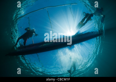 Scuba Divers underneath Outrigger Boat, Cenderawasih Bay, West Papua, Indonesia - Stock Photo