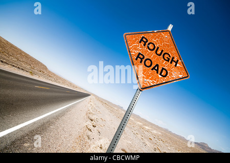 Weathered orange Rough Road warning sign near a tarmac road in Death Valley - Stock Photo