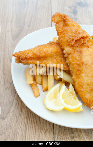 Side view of a plate of fried fish fillets with chips - Stock Photo