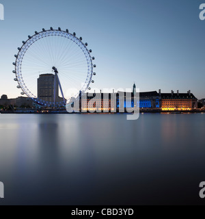 London Eye and building by still river