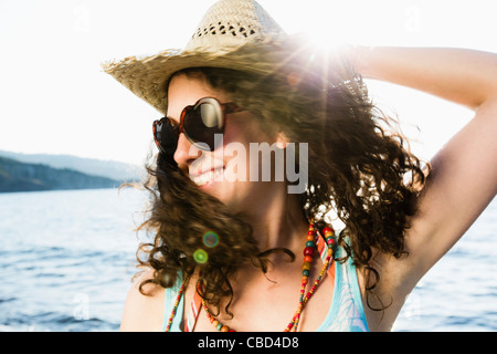 Woman in straw hat smiling on beach - Stock Photo