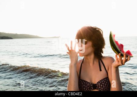 Woman eating watermelon on beach - Stock Photo