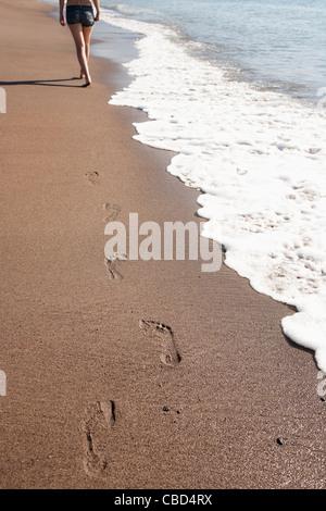 Woman's footprints on beach - Stock Photo