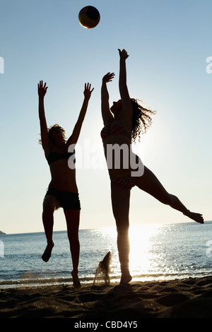 Woman playing with volleyball on beach - Stock Photo