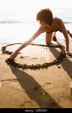 Woman drawing heart in sand on beach - Stock Photo