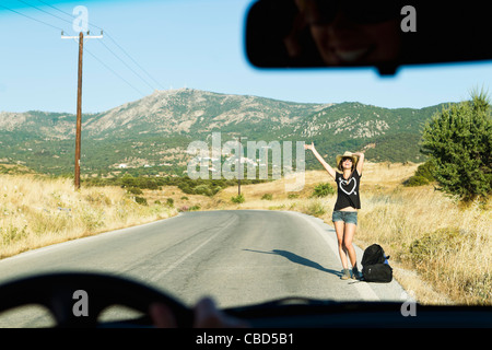 Woman hitch hiking on rural road - Stock Photo