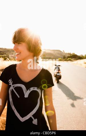 Smiling woman walking on rural road - Stock Photo