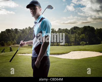 Man carrying golf club on course - Stock Photo