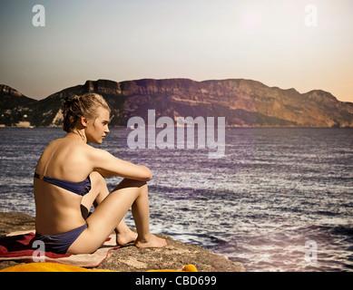 Woman sitting on beach - Stock Photo