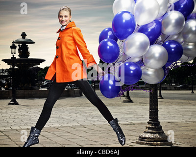 Woman carrying balloons on city street - Stock Photo