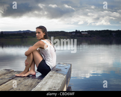 Woman sitting on dock by lake - Stock Photo