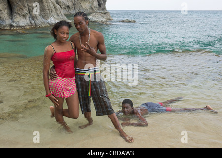 Young locals posing on the beach at Rendezvous Bay, Montserrat - Stock Photo