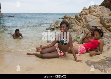 Young locals relaxing on the beach at Rendezvous Bay, Montserrat - Stock Photo