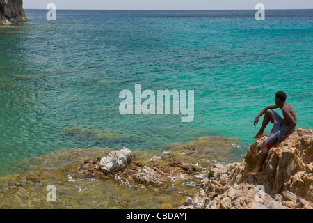 Fisherman sitting on a rock and staring in to the turquoise waters of Rendezvous Bay, Montserrat - Stock Photo