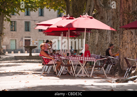 People enjoying drinks under umbrellas on a hot summer day at a pavement cafe in the town centre of Gignac Herault - Stock Photo