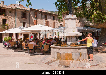 People enjoying drinks on a hot summerday at a pavement cafe by fountain in the hill top village of St Guilhem le - Stock Photo