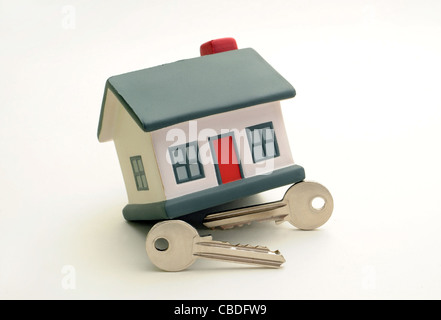 MODEL HOUSE WITH HOUSE KEYS RE HOUSING MARKET RECESSION  CREDIT CRUNCH INCOMES WAGES  MORTGAGES COSTS BILLS DOWNTURN - Stock Photo