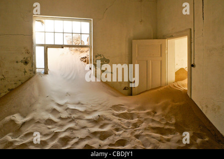 Room in building at abandoned diamond mining town of Kolmanskop, Namibia - Stock Photo