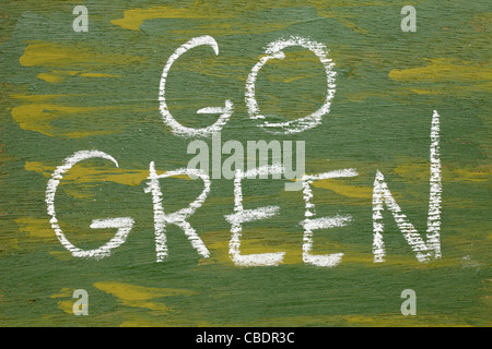 go green sign - white chalk handwriting on plywood board painted green - Stock Photo