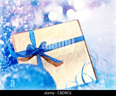 Golden blue gift box with baubles decorations, Christmas tree ornament for winter holidays, present with abstract - Stock Photo