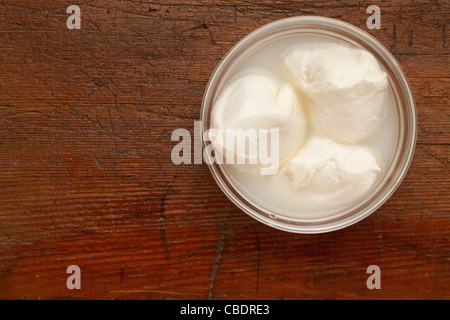 three balls of fresh mozzarella cheese in a glass bowl on scratched grunge wood surface - Stock Photo