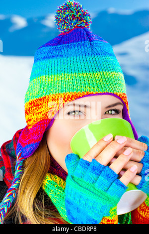 Beautiful girl drinking hot chocolate outdoor in winter, happy female teen in colorful hat, young pretty woman face, - Stock Photo