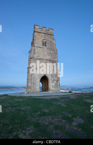 St Michael's at the top of Glastonbury Tor before sunset with mist in the background - Stock Photo