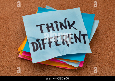 think different concept - motivational phrase on a stack of sticky notes against cork bulletin board - Stock Photo