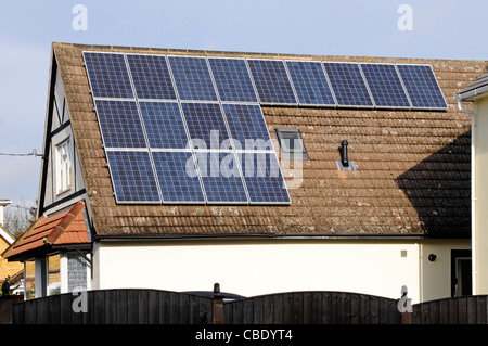 Solar Panels in sunshine installed on south facing roof on sunny blue sky day detached house alongside an existing - Stock Photo