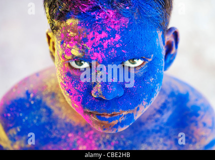 Young Indian boy covered in coloured powder pigment - Stock Photo